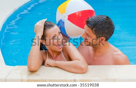 Happy vacations couple in love enjoying summertime in swimmingpool with water ball