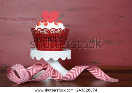 Happy Valentine red velvet cupcake with love messages on red vintage wood background with copy space. - stock photo