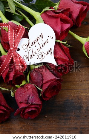 Happy Valentine's Day red roses on dark recycled wood background with greeting on heart shape gift tag - vertical. . - stock photo