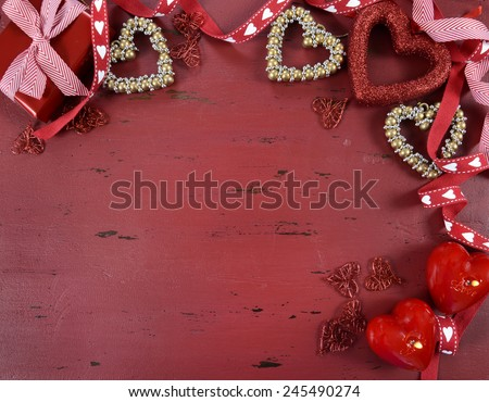 Happy Valentine's Day red vintage wood background with gold hearts and ribbons decorations, with copy space for your text here. - stock photo