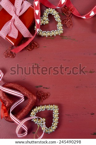 Happy Valentine's Day red vintage wood background with gold hearts and ribbons decorations, with copy space for your text here, vertical. - stock photo