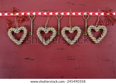Happy Valentine's Day red vintage wood background with hanging gold hearts and ribbon decorations, with copy space for your text here. - stock photo