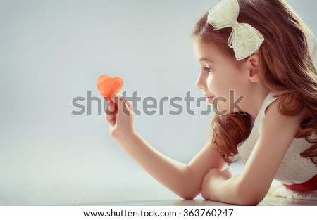 Happy Valentine's Day! Sweet child girl with red heart. Wedding and Valentine concept.