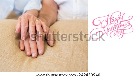 happy valentines day against retired couple holding hands - stock photo