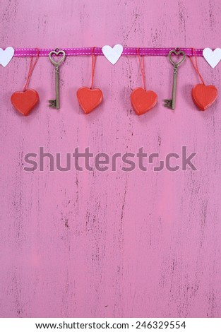 Happy Valentines Day background with hanging heart and key decorations with copy space, vertical. - stock photo
