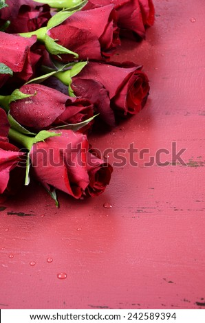 Happy Valentines Day background with red roses close up on distressed vintage recycled wood table. Vertical. - stock photo