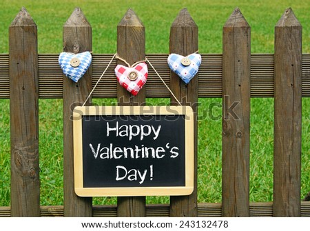 Happy Valentines Day - blackboard with three hearts on garden fence - stock photo