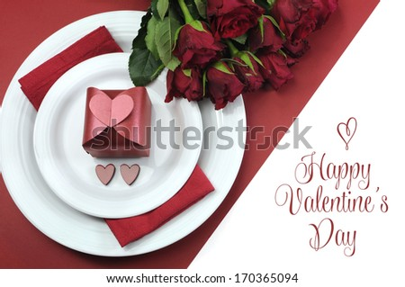 Happy Valentines Day dining table setting, with red hearts, gift, and red roses, with greeting. - stock photo