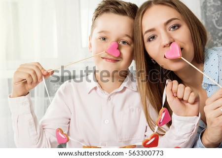 Happy Valentines Day or Mother day. Young boy spend time with her mum and celebrate with gingerbread heart cookies on a stick.