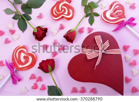 Happy Valentines Day pink background with scattered lollipops, roses and heart shaped gift.  - stock photo