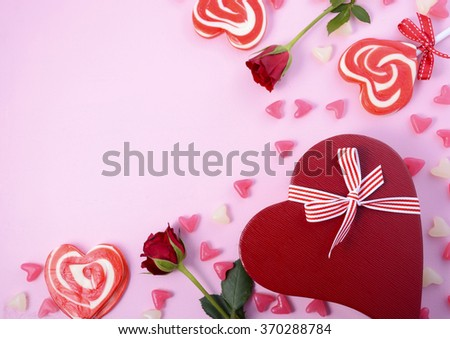 Happy Valentines Day pink background with scattered lollipops, roses and heart shaped gift, with copy space for your text here.  - stock photo