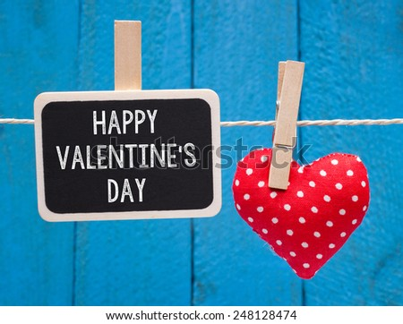 Happy Valentines Day - Red fabric heart with small chalkboard on blue wooden background - stock photo