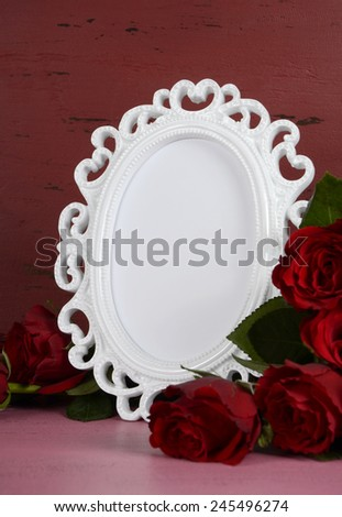 Happy Valentines Day romantic vintage style white photo frame against red and pink rustic wood background with bouquet of red roses, vertical with copy space for your text here. - stock photo