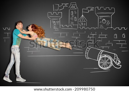 Happy valentines love story concept of a romantic couple against chalk drawings background. Male catching his girlfriend launched as a human cannonball. - stock photo