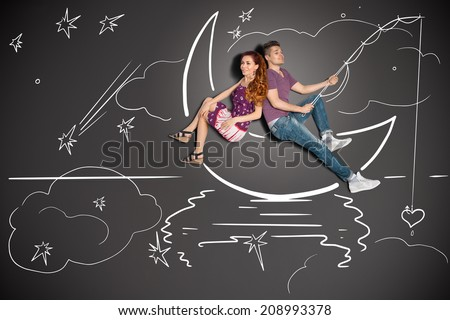 Happy valentines love story concept of a romantic couple fishing on a moon with a heart on a hook against chalk drawings background. - stock photo