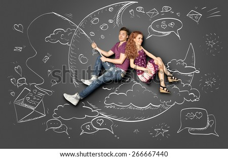Happy valentines love story concept of a romantic couple fishing on a moon with a paper letter on a hook against chalk drawings background. - stock photo