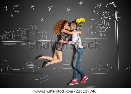 Happy valentines love story concept of a romantic couple having a date under the lantern on the quay against chalk drawings background. - stock photo