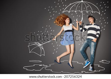 Happy valentines love story concept of a romantic couple in the rain against chalk drawings background. - stock photo