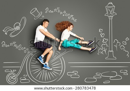 Happy valentines love story concept of a romantic couple on chalk drawings background. Male riding his girlfriend on a vintage penny-farthing bicycle. - stock photo