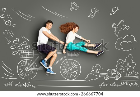 Happy valentines love story concept of a romantic couple on chalk drawings background of a countryside. Male riding his girlfriend in a front bicycle basket. - stock photo