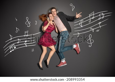 Happy valentines love story concept of a romantic couple sharing headphones and listening to the music against chalk drawings background. - stock photo