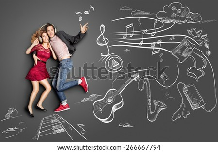 Happy valentines love story concept of a romantic couple sharing headphones and listening to the music against chalk drawings background of musical instruments. - stock photo