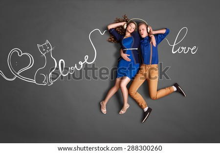 Happy valentines love story concept of a romantic couple sharing headphones and listening to the music about love against chalk drawings background of lyrics. - stock photo