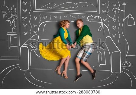 Happy valentines love story concept of a romantic couple sitting on a sofa and holding hands against chalk drawings background of a living room.
