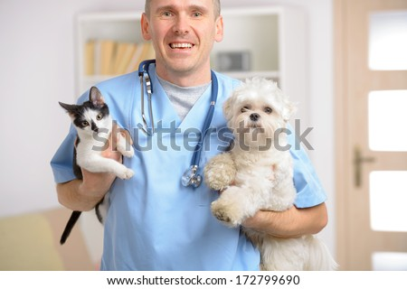Happy vet with dog and cat, focus intentionally left on smile of veterinary. - stock photo