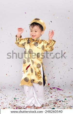 Happy Vietnamese boy celebrating New Year with confetti. Asian Kid Celebrating New Year - stock photo
