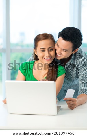 Happy Vietnamese couple using laptop to shop online
