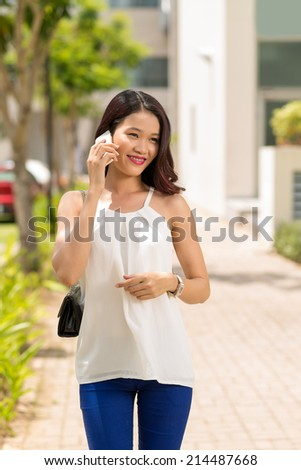 Happy Vietnamese girl talking on the phone and walking along the street - stock photo