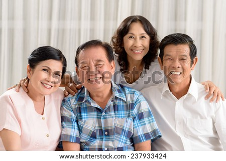 Happy Vietnamese senior people bonding together and looking at the camera - stock photo