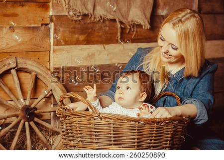 Happy village family, mom playing with a baby in a basket sitting on the hay. Little girl sitting in a basket with hay - stock photo