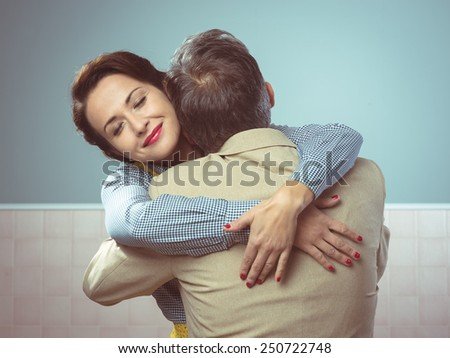 Happy vintage couple 1950s style smiling and hugging - stock photo