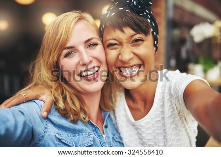 Happy vivacious attractive young multiracial girlfriends grinning happily at the camera as they standing arm in arm laughing and joking - stock photo