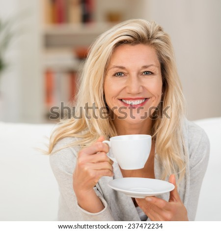 Happy vivacious middle-aged blond woman holding a cup of tea or coffee looking at the camera with a beaming warm smile - stock photo