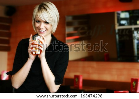 Happy vivacious young blond woman drinking orange juice or cocktail cradling the glass in her hands as she glances down at the floor - stock photo