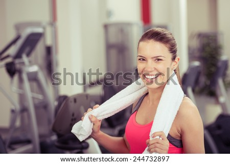 Happy vivacious young woman in a gym standing surrounded by equipment with a towel around her shoulders smiling at the camera, head and shoulders in a fitness concept