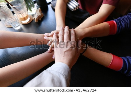 Happy volunteer family putting their hands together  - stock photo