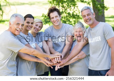 Happy volunteer family putting their hands together on a sunny day - stock photo