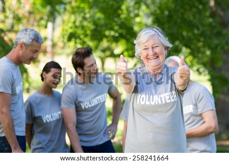 Happy volunteer grandmother with thumbs up on a sunny day - stock photo