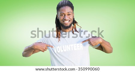 Happy volunteer in the park against green vignette