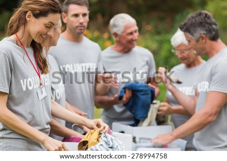 Happy volunteer looking at donation box on a sunny day - stock photo