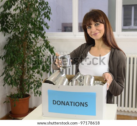 happy volunteer woman with food donation box - stock photo