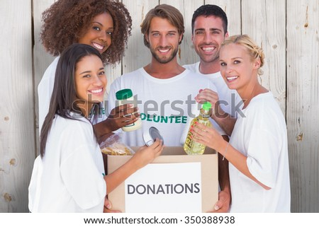 Happy volunteers putting food in donation box against wooden background - stock photo
