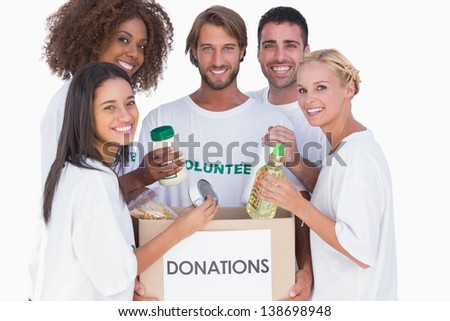 Happy volunteers putting food in donation box on white background - stock photo