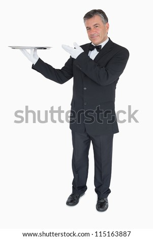 Happy waiter presenting an empty silver tray