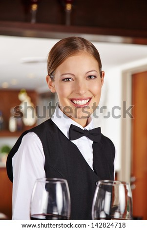 Happy waiter with two red wine glasses in hotel - stock photo