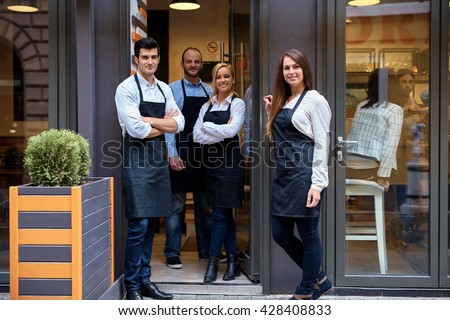Happy waiters and waitresses standing at the entrance of cafeteria, smiling, looking at camera, wearing apron.